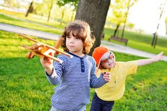 Boys with curly hair play a wooden toy airplane in the park. stock images