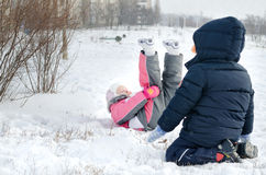 Two small children frolicking in the snow. Two small children frolicking  snow with  little girl lying on her back with her legs in air fashionable pink winter Stock Photo