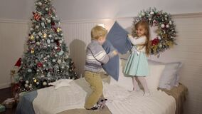 Two children fight pillows on the bed at home. Two small children jump on the bed and fight with pillows of the house in the Christmas interior. Little brothers stock footage