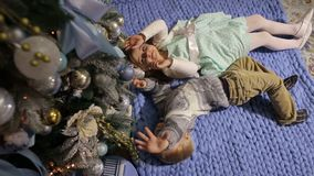 Two children lie on the floor near Christmas tree. Two small children lie on the floor and look at the Christmas tree from the bottom up stock footage