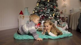 A little boy kisses a girl near a Christmas tree. Two small children lie on the floor next to a decorated Christmas tree, the boy kisses the girl. Happy stock footage