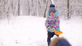 Two small children play with snow in winter Park. Wintertime stock video footage