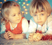 Two small children playing with christmas decoration. Small boy and his sister lying on a floor and playing with Christmas decoration Stock Image