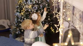 Two small children playing near the Christmas tree. Two small children play with Christmas toys near the fireplace and decorated Christmas tree. Christmas star stock footage