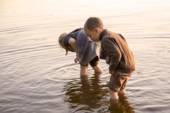Two small children are playing in the river.  Royalty Free Stock Images