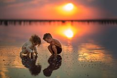 Two small children playing on the seashore during sunset. Reflection in water royalty free stock image