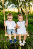 Two small children are riding on a swing outdoors Stock Images