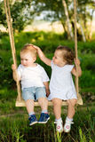 Two small children are riding on a swing outdoors Stock Photo