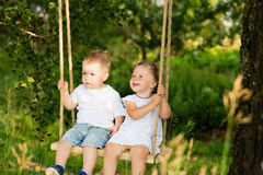 Two small children are riding on a swing outdoors Royalty Free Stock Photo