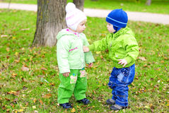 Two small children sit on a green clearing Royalty Free Stock Photography