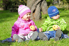 Two small children sit on a green clearing. Eat apples Stock Photos