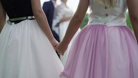Two small chlidren girls holding hands looking at bride and groom embracing lovely couple embracing on background stock video