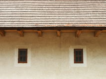 Two small closed wooden windows. Part of the roof and two small closed wooden window in the facade of a medieval castle Zvikov (Czech republic royalty free stock photography