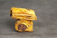 Crispy sausage rolls on a dark surface. Two small cooked sausage rolls on a dark slate effect surface stock image