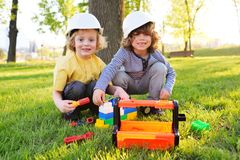 Cute children in building helmets play in workers or builders with toy tools in a park on the grass. stock photo
