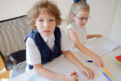 Two small disciples of an elementary school sit at a desk. Stock Photos