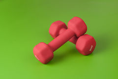 Two small dumbbells on green Royalty Free Stock Photos