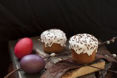 A two small Easter cake and dyed eggs, and a willow twig on a dark wooden background. Close up. Selective focus Stock Image
