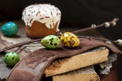 A two small Easter cake and dyed quail  eggs, and a willow twig on a dark wooden background. A two small Easter cake and dyed quail eggs, and a willow twig on a Stock Images