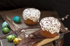 A two small Easter cake and dyed quail  eggs, and a willow twig on a dark wooden background. A two small Easter cake and dyed quail eggs, and a willow twig on a Stock Photo