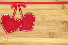 Two small felt hearts in the left corner on wooden background. Two felt hearts on wooden background for valentines day, suitable for greeting card, restaurant stock photo