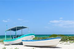 Two small fishing boats tied together on tropical beach Royalty Free Stock Images