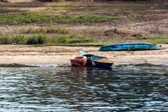 Two small fishing boats, typical of the Nile river, one on the shore of the river and the other on dry land with the keel up. Both stock photo