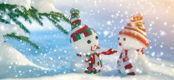Two small funny toys baby snowman in knitted hats and scarves in stock photo
