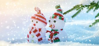 Two small funny toys baby snowman in knitted hats and scarves in royalty free stock photo