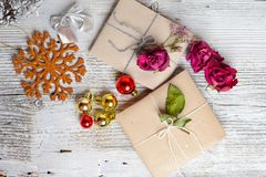 Two small gifts wrapped in ecologic paper, old wooden white table. Two small gifts wrapped in ecologic paper, Christmas decorations. Boxes decorated with dried stock images