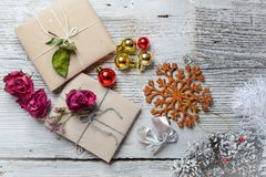 Two small gifts wrapped in ecologic paper, old wooden white table. Two small gifts wrapped in ecologic paper, Christmas decorations. Boxes decorated with dried stock photo