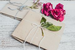 Two small gifts wrapped in ecologic paper, old wooden white table. Two small gifts wrapped in ecologic paper, snowflake, Christmas decorations. Boxes decorated royalty free stock photo