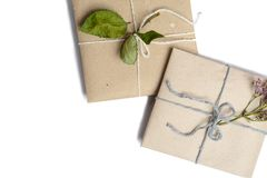 Two small gifts wrapped in ecologic paper, white isolated with space for text writing. Boxes decorated with dried flowers and leaves stock image