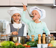 Two small  girls cooking vegetable soup. Two small smiling happy girls cooking vegetable soup at home kitchen Stock Images