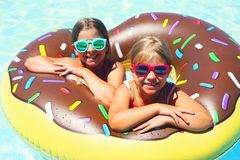 Two small girls having fun in pool Stock Photography