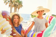Two small girls with inflatable toys on the beach Stock Images