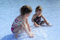 Two small girls are playing in the swimming pool Royalty Free Stock Photos