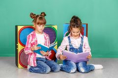 Two small girls read books in the children`s room. The concept o royalty free stock photos