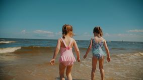 Two small girls run on the beach in summer. Two small and adorable girls run on the beach by the sea in summer stock footage