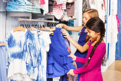 Two small girls shop together in the clothes store Stock Image