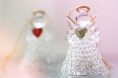 Two small glass angel statuettes with hearts. In their hands. The concept of peace ad love royalty free stock photos