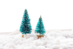 Two small green toy Christmas tree on a wooden background as  symbol of the new year with place for text, next to white Stock Images
