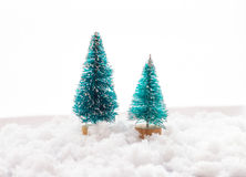 Two small green toy Christmas tree on a wooden background as  symbol of the new year with place for text, next to white Stock Photos