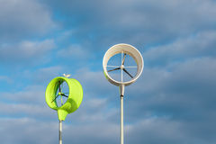 Two small wind turbines against a blue cloudy sky Stock Images