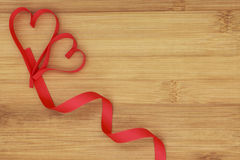Two small hearts in the left corner on wooden background. Two small hearts with curved ribbon on the bottom on wooden background for valentines day, suitable for royalty free stock image