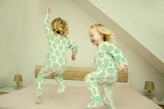 Two small identical twin sisters in identical pajamas, actively having fun on the parent& x27;s bed, Royalty Free Stock Images