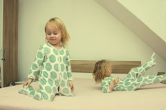 Two small identical twin sisters in identical pajamas, actively having fun on the parent& x27;s bed, Stock Image