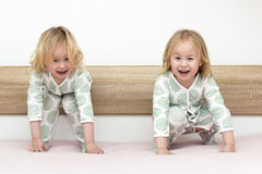 Two small identical twin sisters in identical pajamas, actively having fun on the parent& x27;s bed, Stock Photography