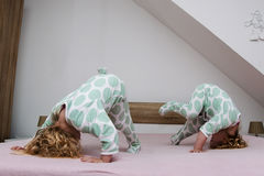 Two small identical twin sisters in identical pajamas, actively having fun on the parent& x27;s bed, Stock Photo