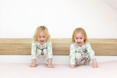 Two small identical twin sisters in identical pajamas, actively having fun on the parent& x27;s bed, Royalty Free Stock Image